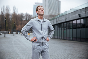 Tired runner in gray sportswear standing on the street with arms at hips
