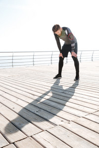 Tired runner near the sea. full length image. side view. looking down