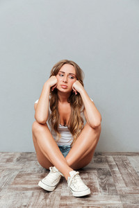 Tired upset young woman sitting with legs crossed and having headache over gray background