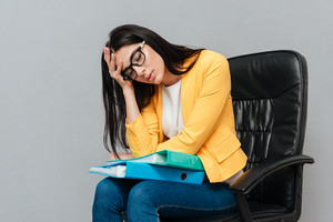 Tired woman wearing eyeglasses and dressed in yellow jacket holding folders while sitting on office chair over grey background. Eyes closed.