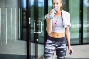 Tired Young Woman Drinking Water After Workout