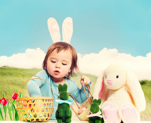 Toddler girl collecting Easter eggs with bunny companions