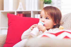 Toddler girl drinking milk on her living room sofa