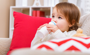 Toddler girl drinking milk on her living room sofa