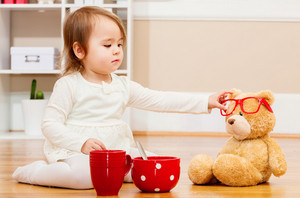 Toddler girl having tea time with her teddy bear in her house