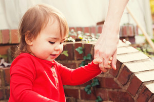Toddler girl holding hands with her father outside in autumn