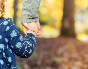 Toddler girl holding hands with her mother outside on a fall day