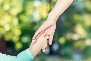 Toddler girl holding hands with her mother outside