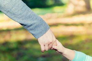 Toddler girl holding hands with her parent outside