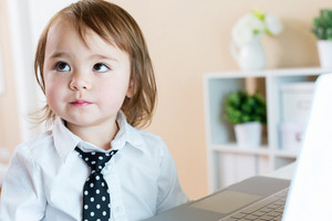 Toddler girl in a dress shirt and tie sitting at a laptop