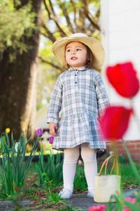 Toddler girl in a hat exploring her garden in spring