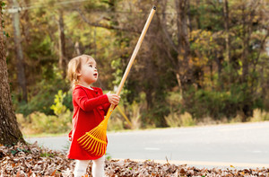 Toddler girl in a red shirt playing with a rake outside in autumn