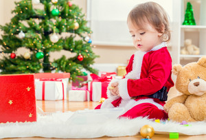 Toddler girl in a santa suit playing by the Christmas tree