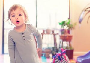 Toddler girl in blue dress in her house