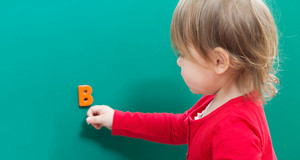 Toddler girl learning her alphabet letters on a chalkboard