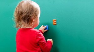 Toddler girl learning her letters on a chalkboard
