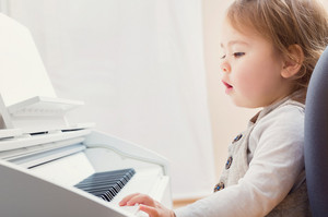 Toddler girl learning how to play piano