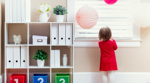 Toddler girl peeking out of the window in her house