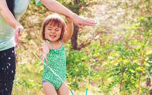 Toddler girl playing in a sprinkler with her mother outside on a summer day