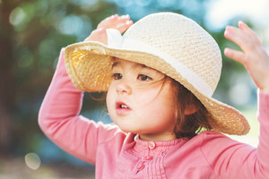 Toddler girl playing outside in a hat