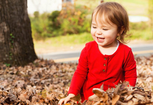 Toddler girl playing outside in a pile of autumn leaves