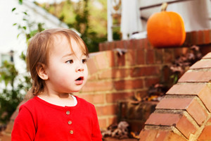 Toddler girl playing outside in the autumn
