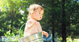 Toddler girl playing outside with a bucket
