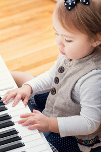 Toddler girl playing piano from above