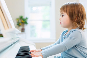 Toddler girl playing the piano in her house