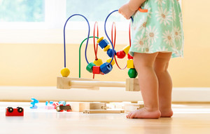 Toddler girl playing with colorful toys in a bright room