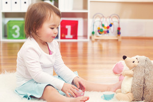 Toddler girl playing with her stuffed animals in her house