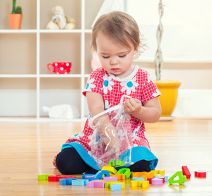 Toddler girl playing with her toys inside her house