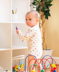Toddler girl playing with toys in her house