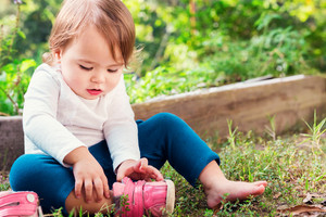 Toddler girl putting on her sneakers outside
