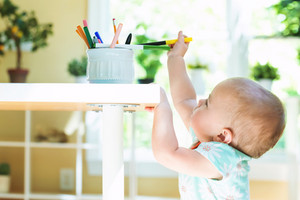 Toddler girl reaching for a jar of markers