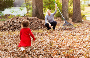 Toddler girl running to her father outside raking leaves in the fall