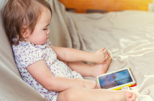 Toddler girl watching cartoons on her tablet computer