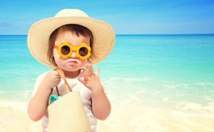 Toddler girl wearing a hat and sunglasses at the beach in summer
