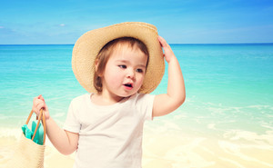 Toddler girl wearing a hat at the beach in summer