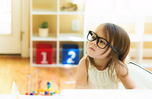 Toddler girl wearing glasses in her house