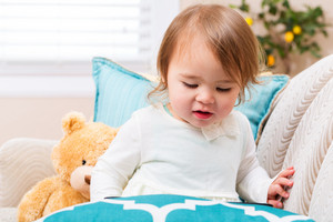 Toddler girl with a tablet computer in her living room