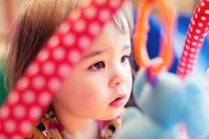 Toddler girl with colorful toys in her house