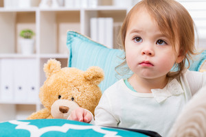 Toddler girl with her teddy bear and tablet computer