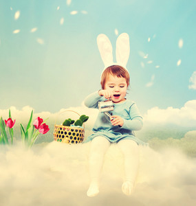 Toddler girl with rabbit ears in Easter theme