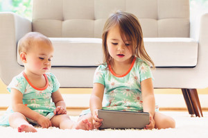 Toddler sisters watching a tablet computer in their living room