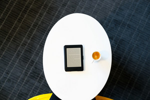 Top down view of digital e-book device with coffee