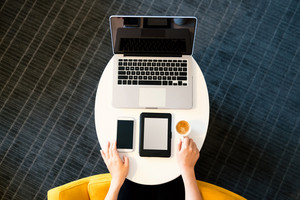 Top down view of woman with digital devices and coffee