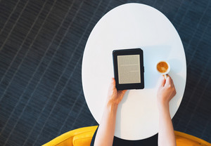 Top down view on small digital ebook reader and coffee in hands of person