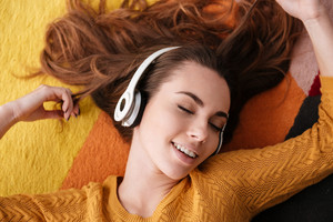 Top view close up portrait of a young pretty girl in headphones enjoying music while lying on a carpet at home with eyes closed