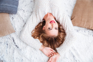 Top view of a beautiful smiling woman wearing red lipstick and sweater lying on the carpet
